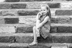 Малый усмехаясь ребёнок в голубом платье на красочных лестницах Стоковое фото RF