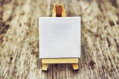 Малый чистый мольберт на деревянной предпосылке Абстракция для мыслей и идей Белый мольберт Стоковые Фото