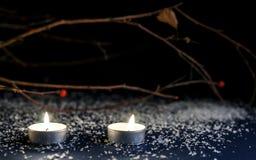 2 малых горящих свечи на таблице Стоковые Изображения