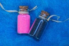 2 малых декоративных стеклянных бутылки с красным цветом и отработанной формовочной смесью стоковое фото rf
