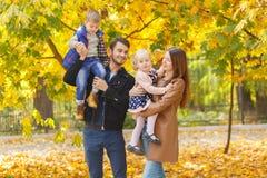 2 малых дет, мальчик и девушка сидят в их руках ` родителей в парке осени стоковая фотография rf