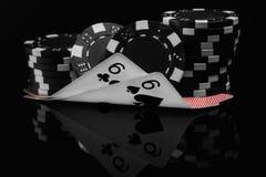 2 малых карточки в покере под обломоками покера отразили на черной предпосылке Стоковые Фото