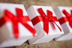 3 малых подарочной коробки для настоящих моментов на деревянном столе Стоковые Фотографии RF