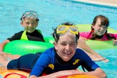 малыши играя заплывание бассеина стоковое изображение