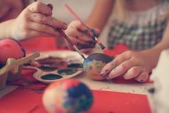 Малыши имея потеху крася пасхальные яйца Стоковые Изображения