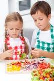 малыши подготовляя veggies ручки Стоковая Фотография