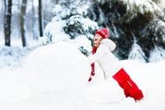 Малыши строя снеговик Дети в снежке управлять зимой розвальней потехи Стоковая Фотография