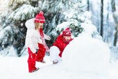 Малыши строя снеговик Дети в снежке управлять зимой розвальней потехи Стоковые Изображения RF