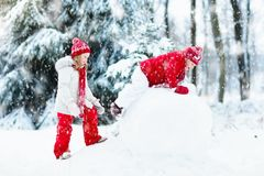 Малыши строя снеговик Дети в снежке управлять зимой розвальней потехи Стоковые Изображения