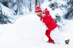 Малыши строя снеговик Дети в снежке управлять зимой розвальней потехи Стоковое Изображение