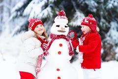 Малыши строя снеговик Дети в снежке управлять зимой розвальней потехи Стоковое Фото