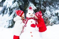Малыши строя снеговик Дети в снежке управлять зимой розвальней потехи стоковые фотографии rf