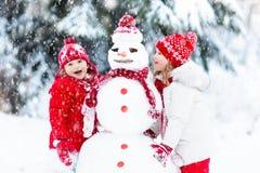 Малыши строя снеговик Дети в снежке управлять зимой розвальней потехи стоковое изображение rf