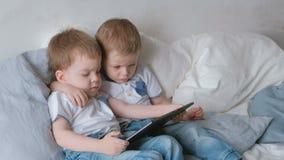 Малыши с таблеткой 2 малыша близнецов мальчиков смотря шарж на таблетке лежа на кровати видеоматериал