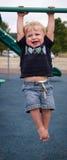 Малыш вися от штанг стоковое изображение