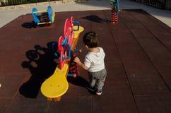 Малыш играя самостоятельно в парке - сиротливом ребенке стоковое фото rf