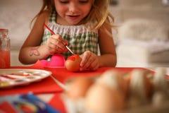 Малыш имея потеху крася пасхальные яйца Стоковое фото RF