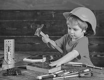 Малыш на занятой стороне играет с инструментом молотка дома в мастерской Игра мальчика ребенк как разнорабочий Ребенок в играть ш стоковое фото rf