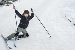 Малыш падает на лыжу в горе снега зимы стоковые изображения
