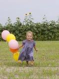 малыш поля воздушных шаров счастливый идущий Стоковое Изображение RF