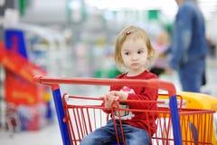 малыш прелестной покупкы тележки сидя стоковое изображение rf