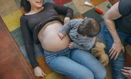 Малыш щекоча живот его беременной матери стоковое фото