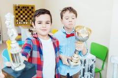 2 мальчика выигрывая трофей удерживания турнира шахмат стоковая фотография rf
