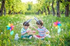 2 мальчика в парке, имеющ потеху с покрашенными яичками для пасхи Стоковые Фото