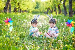 2 мальчика в парке, имеющ потеху с покрашенными яичками для пасхи Стоковое Изображение