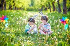 2 мальчика в парке, имеющ потеху с покрашенными яичками для пасхи Стоковое Фото