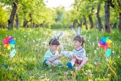 2 мальчика в парке, имеющ потеху с покрашенными яичками для пасхи Стоковая Фотография