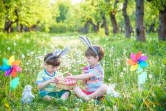 2 мальчика в парке, имеющ потеху с покрашенными яичками для пасхи Стоковые Фотографии RF