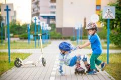 2 мальчика в парке, мальчике помощи с коньками ролика, который нужно стоять вверх Стоковая Фотография RF