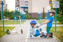 2 мальчика в парке, мальчике помощи с коньками ролика, который нужно стоять вверх Стоковое Изображение RF