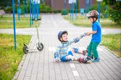 2 мальчика в парке, мальчике помощи с коньками ролика, который нужно стоять вверх Стоковое фото RF