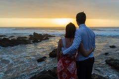 Мальчика девушки Silhouetted утесы океана совместно счастливые Стоковое Изображение