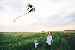 2 мальчика запуская змея на предпосылке хранят пшеницей, который Зачатие братства стоковое изображение rf