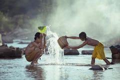 2 мальчика играют выплеск в потоке Стоковые Изображения RF