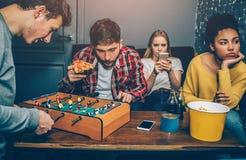 2 мальчика играют футбольную игру доски Они очень сконцентрированы на ем пока девушки наблюдают в телефоне и Стоковое Изображение