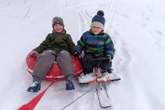2 мальчика идут sledding и трубопровод снега стоковая фотография
