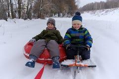 2 мальчика идут sledding и трубопровод снега стоковые фото