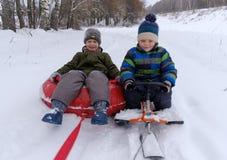 2 мальчика идут sledding и трубопровод снега стоковая фотография rf