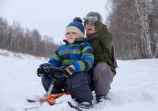 2 мальчика идут sledding и трубопровод снега стоковое фото
