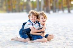 2 мальчика маленьких ребеят имея потеху на тропическом пляже Стоковое Изображение