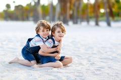 2 мальчика маленьких ребеят имея потеху на тропическом пляже Стоковые Изображения RF