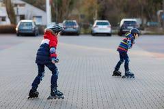 2 мальчика маленьких ребят катаясь на коньках с роликами в городе Счастливые дети, братья и лучшие други в безопасности защиты стоковые изображения