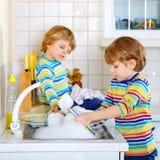 2 мальчика маленького ребенка моя блюда в отечественной кухне Стоковое Изображение