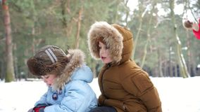 2 мальчика на розвальнях ехать вниз и их шарике снега падения матери сток-видео