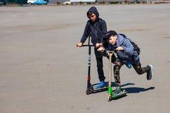 2 мальчика, одного в крышке, другой в клобуке, крен на скутерах нажимая с дороги с улыбками на их стороне вокруг квадрата для стоковое фото