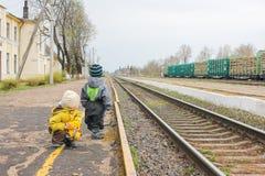 2 мальчика около железной дороги на станции наблюдая поезд CH Стоковое фото RF